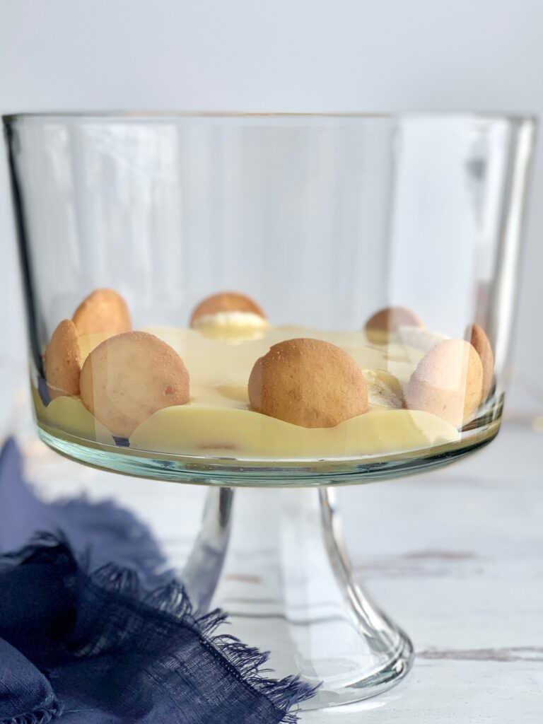 A glass trifle bowl filled with layers of vanilla wafer cookies, sliced bananas, vanilla pudding.