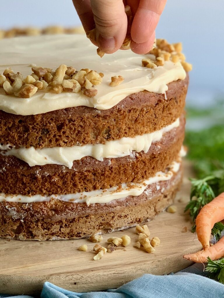 A 3 tiered carrot cake with a white cream cheese frosting in-between each layer and on top with a hand shown sprinkling nuts over the top.