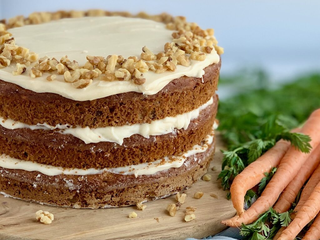 A 3 tiered carrot cake with a white cream cheese frosting in-between each layer and on top with nuts next to a bunch of fresh carrots with long green tops.