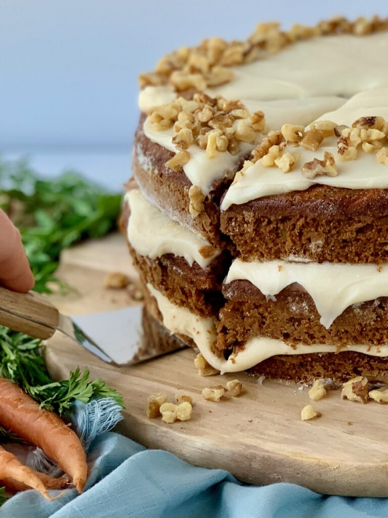 A 3 tiered carrot cake with a white cream cheese frosting in-between each layer and on top with nuts. A slice has been cut out of the cake and is just starting to be lifted up by a serving utensil.
