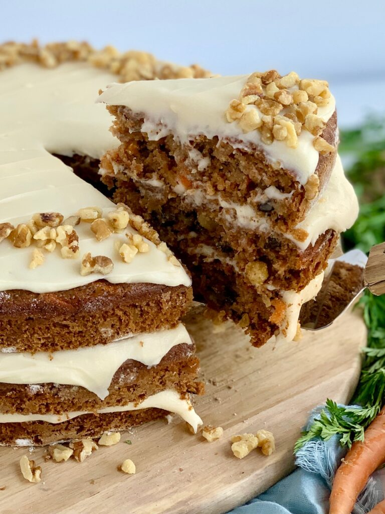 A 3 tiered carrot cake with a white cream cheese frosting in-between each layer and on top with nuts. A slice has been cut out of the cake and is being lifted up by a serving utensil.