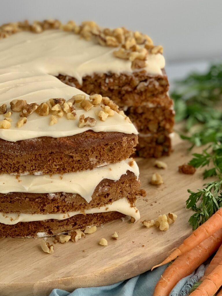 A 3 tiered carrot cake with a white cream cheese frosting in-between each layer and on top with nuts. A slice has been cut out of the cake.