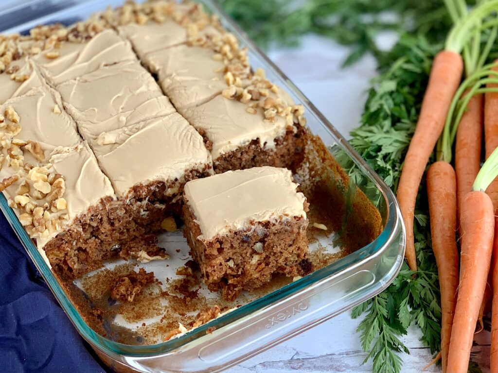 """A 9 x 13"""" cake pan filled with a shredded cake mixture with unsweetened applesauce, crushed pineapple, and topped with a creamy brown sugar cream cheese frosting and chopped walnuts around the outside edge of the cake next to a bunch of carrots. A few pieces of cake have been removed to show the inside of the cake."""