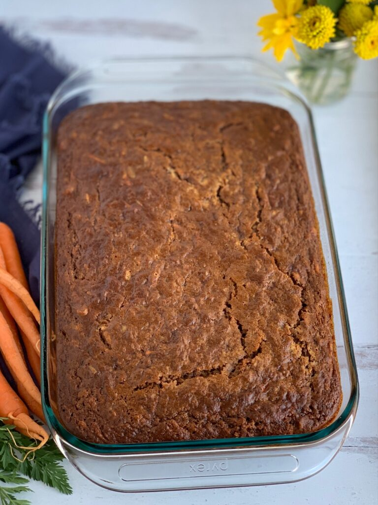 """A moist looking carrot cake in a 9 x 13"""" baking pan with no frosting on it yet."""