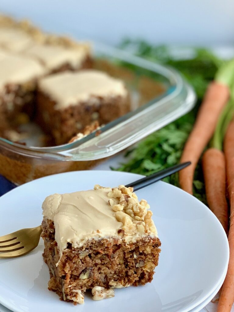 """A 9 x 13"""" baking pan filled with a shredded cake mixture with unsweetened applesauce, crushed pineapple, and topped with a creamy brown sugar cream cheese frosting and chopped walnuts around the outside edge of the cake next to a bunch of carrots. And a slice of cake on a white cake plate next to a fork."""