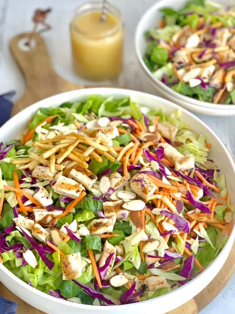a large salad with greens, sliced carrots, toasted almond slivers, and grilled chicken