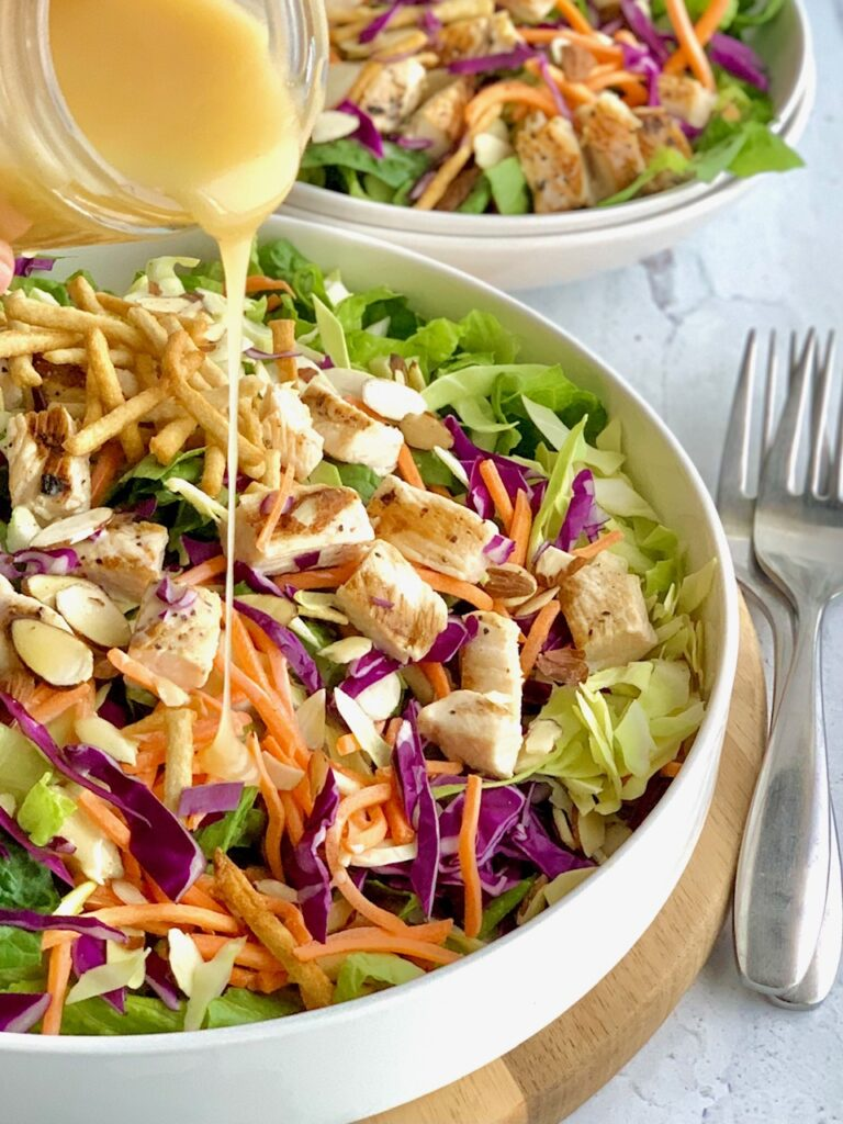 A large salad in a serving platter. The salad has cuts of romaine lettuce, purple cabbage, light green napa cabbage, chunks of grilled chicken, shredded carrots, and lots of sliced almonds. There is even a few strips of wonton strips. Over the top of the salad is a dressing being poured onto it.