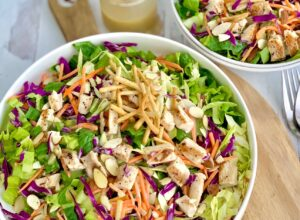 A large salad in a serving platter. The salad has cuts of romaine lettuce, purple cabbage, light green napa cabbage, chunks of grilled chicken, shredded carrots, and lots of sliced almonds. There is even a few strips of wonton strips.