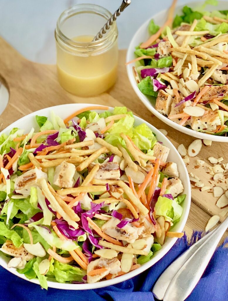 2 small salad serving plates with cuts of romaine lettuce, purple cabbage, light green napa cabbage, chunks of grilled chicken, shredded carrots, and lots of sliced almonds. There is even a few strips of wonton strips.