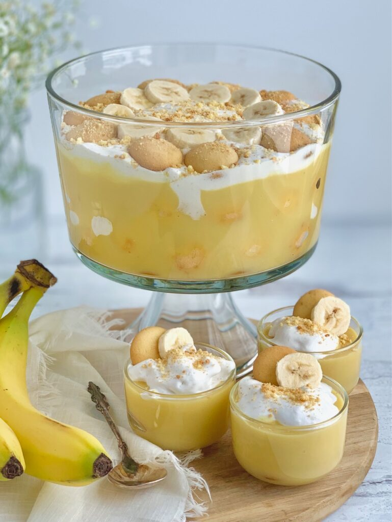 3 mini dessert glasses filled with layers of sliced bananas, vanilla wafer cookies, banana pudding, and creamy whipped topping. Then cookie crumbs, another cookie, and a banana slice on top of that next to a trifle bowl filled with the same layers and toppings.