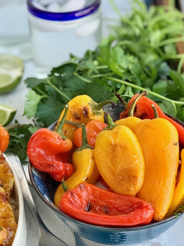 A small bowl filled with grilled sweet peppers.