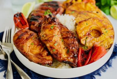 A platter of jasmine white rice with grilled chicken smothered in homemade teriyaki sauce next to grilled pineapple rings and grilled mini sweet peppers with grill marks on them. With 1 blue water cup in the background.
