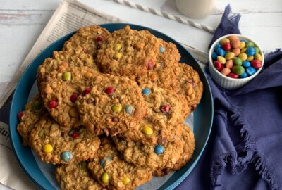 A blue plate full of cookie with oats, creamy peanut butter, chocolate morsels, and chocolate candies.