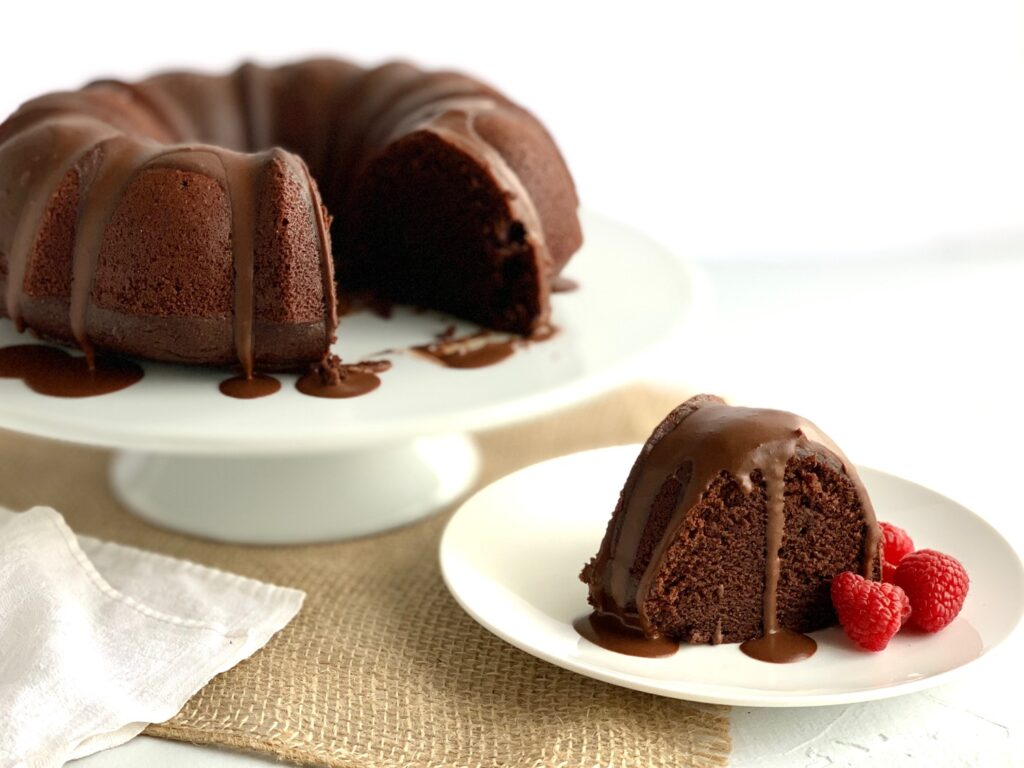 A round chocolate bundt cake with a couple of slices cut out of it. One slices is on a plate next to it with chocolate ganache running down it and fresh raspberries.