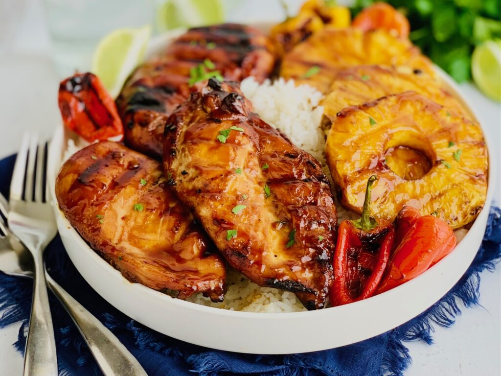 A large serving platter with jasmine rice, grilled chicken, pineapple slices, and min sweet peppers.