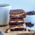A stack of 3 cut bars. The first layer of the bars is a chocolate brownie, with crunchy peanut butter slathered over it, then topped with a soft chocolate marshmallow mixture next to a cup of coffee..