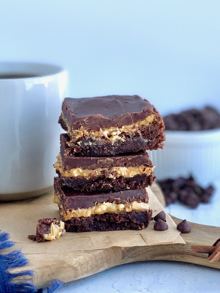 A stack of 3 cut bars. The first layer of the bars is a chocolate brownie, with crunchy peanut butter slathered over it, then topped with a soft chocolate marshmallow mixture next to a cup of coffee.