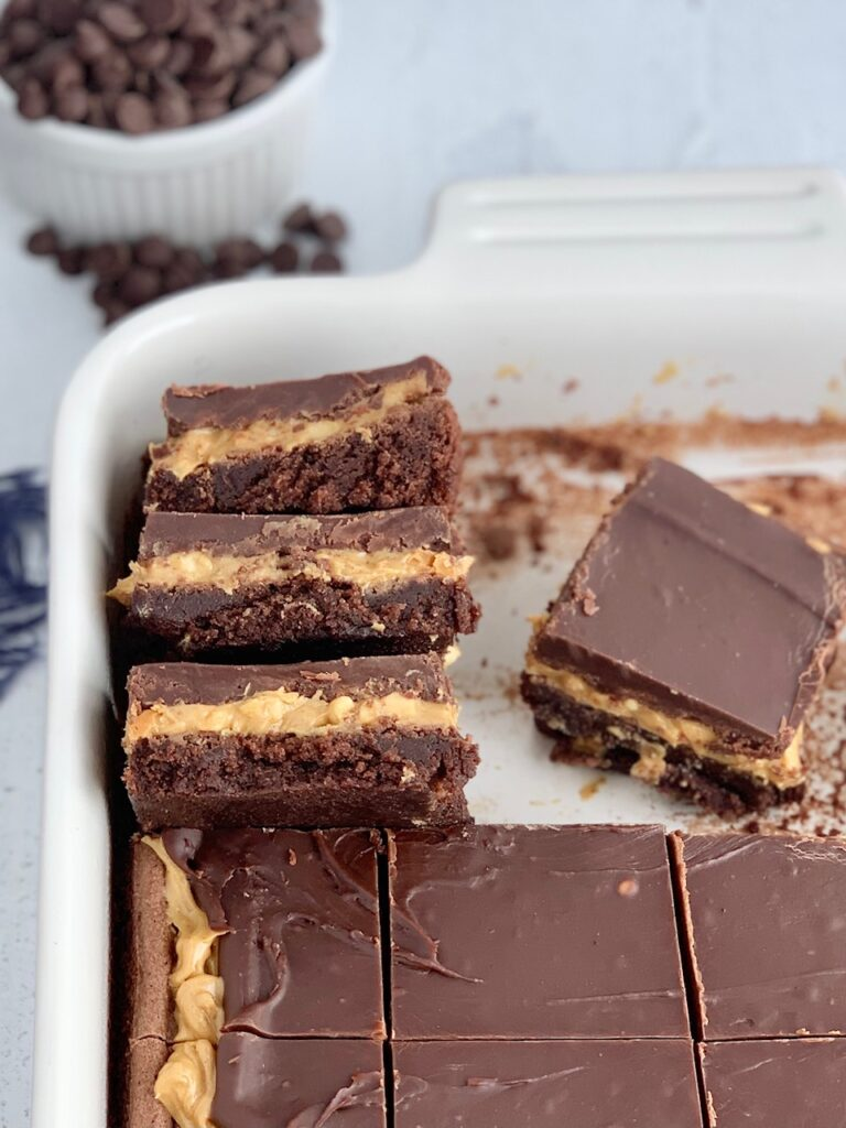 A stack of 3 cut bars. The first layer of the bars is a chocolate brownie, with crunchy peanut butter slathered over it, then topped with a soft chocolate marshmallow mixture in a baking pan with more cut bars.