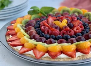 A round sugar cookie in a pizza pan with a cream cheese mixture spread on it. Then it's topped with fresh sliced fruit such as strawberries, kiwi, grapes, and raspberries.,