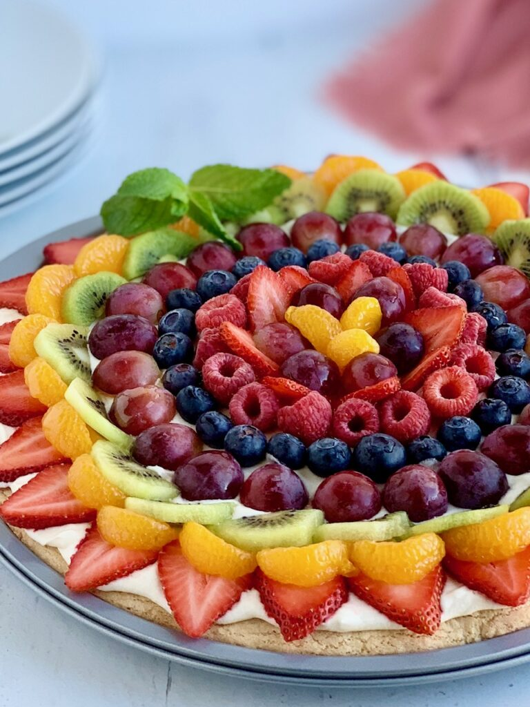 A pizza pan with a sugar cookie baked in it and topped with a cream cheese spread. Then various sliced fruits such as strawberries, mandarin oranges, kiwi,  grapes, blueberries, raspberries next to several serving plates.