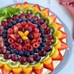 A round pizza pan filled with a soft sugar cookie crust, then topped with a cream cheese spread. The top layer is several different sliced fruits such as strawberries, kiwi, grapes, blueberries, raspberries, and mandarin oranges next to a pink colored kitchen towel.