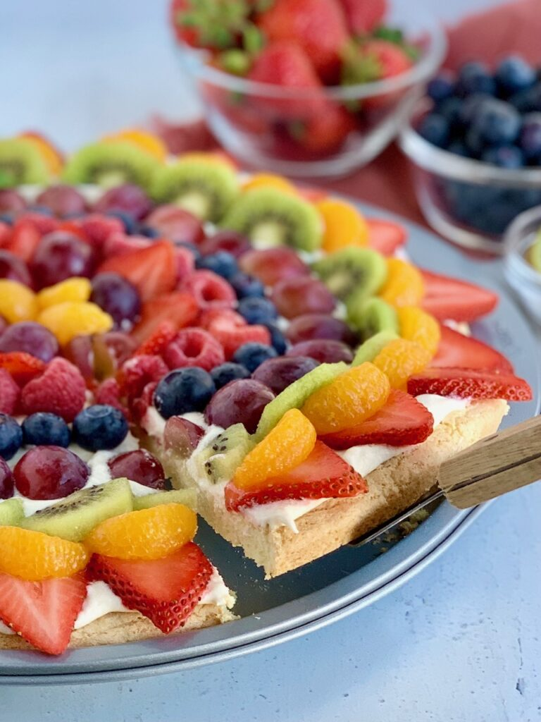 A pizza pan with a sugar cookie baked in it and topped with a cream cheese spread. Then various sliced fruits such as strawberries, mandarin oranges, kiwi,  grapes, blueberries, raspberries next to several bowls of fruit. A serving utensil is under a slice of of the fruit and moving it.