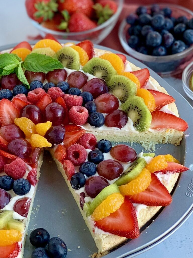 A pizza pan with a sugar cookie baked in it and topped with a cream cheese spread. Then various sliced fruits such as strawberries, mandarin oranges, kiwi,  grapes, blueberries, raspberries next to several bowls of fruits and the fruit pizza cut into slices and some is gone.