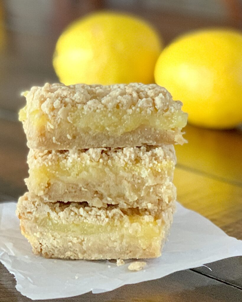 3 lemon bars stacked  on top of each other. Each bar has a thick crust followed by a lemon filling and then topped with a streusel.