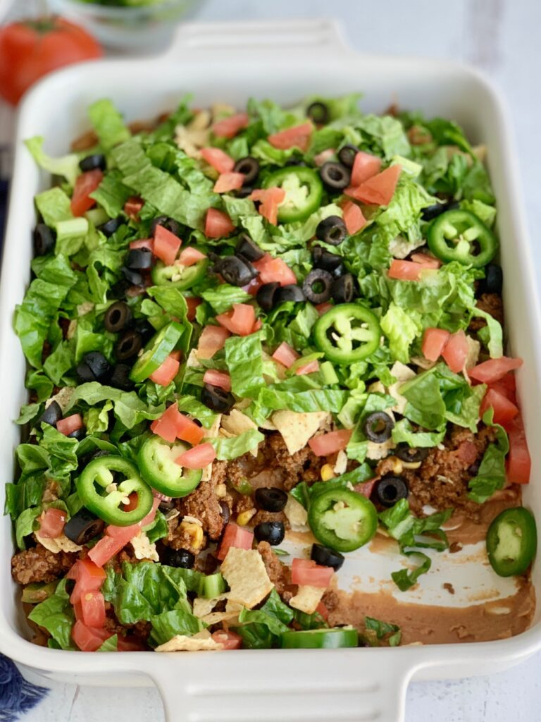A baking dish filled with a layer of refried beans, taco meat sauce, crunched up chips, shredded romaine lettuce, diced tomatoes, jalapeno peppers, and black olives with some of it removed.