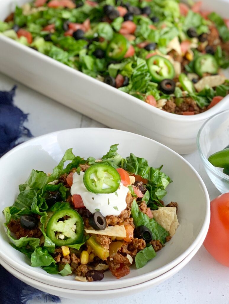 A dinner bowl filled with refried beans, taco meat sauce, crunched up chips, shredded romaine lettuce, diced tomatoes, jalapeno peppers, and black olives. Then topped with a dollop of dairy free sour cream,