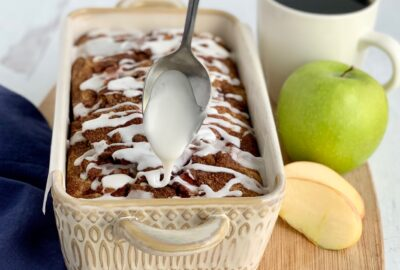 A loaf of bread still in the pan with a spoon drizzling white drizzle across the top in a zig zag motion next to a green Granny Smith apple and a cup of coffee.
