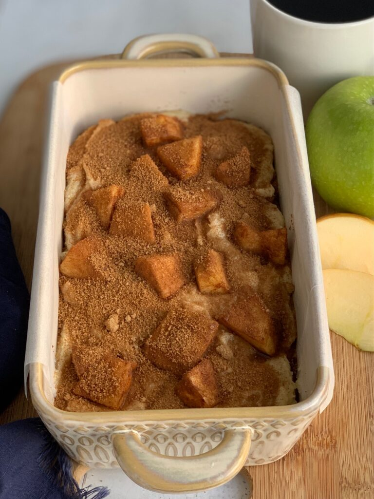 A loaf pan full of batter topped with apple chunks covered in cinnamon and sugar and topped with another layer of cinnamon and sugar.