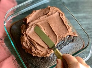 A glass pan holding a baked chocolate cake with a person spreading chocolate buttercream frosting on it.