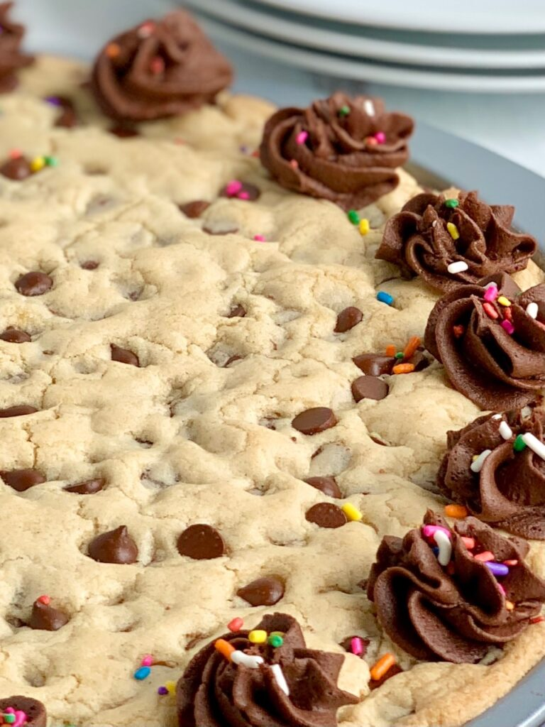 A close up of a giant chocolate chip cookie on a pizza pan with chocolate frosting swirls around the outside of the cookie. And colorful sprinkles are on top of the frosting.