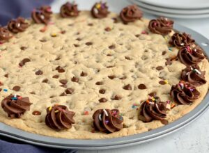 A giant chocolate chip cookie in a pizza pan with chocolate buttercream frosting swirls around the outside edge. And sprinkles are on top of it next to serving plates.