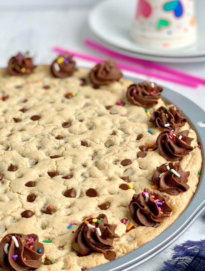 A giant chocolate chip cookie on a pizza pan with chocolate frosting swirls around the outside of the cookie. And colorful sprinkles are on top of the frosting. White plates with party cups on top of them are in the background.