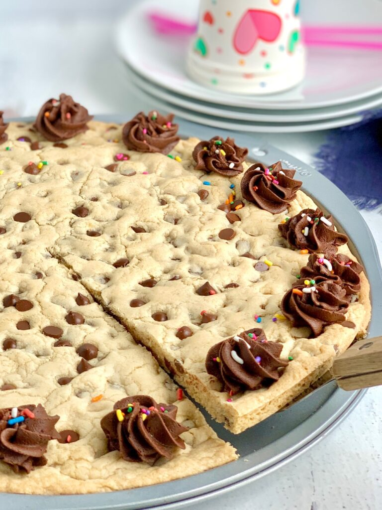 A giant chocolate chip cookie on a pizza pan with chocolate frosting swirls around the outside of the cookie. And colorful sprinkles are on top of the frosting. A slice has been cut and a pie server is removing it.