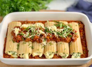 A white baking pan filled with ground beef and marinara topped with 6 soft round and long manicotti pasta shells. Each shell is filled with a creamy looking white ricotta mixture. Then more ground beef and marinara sauce is spread over that with dairy free shredded cheese and spinach on top of that.