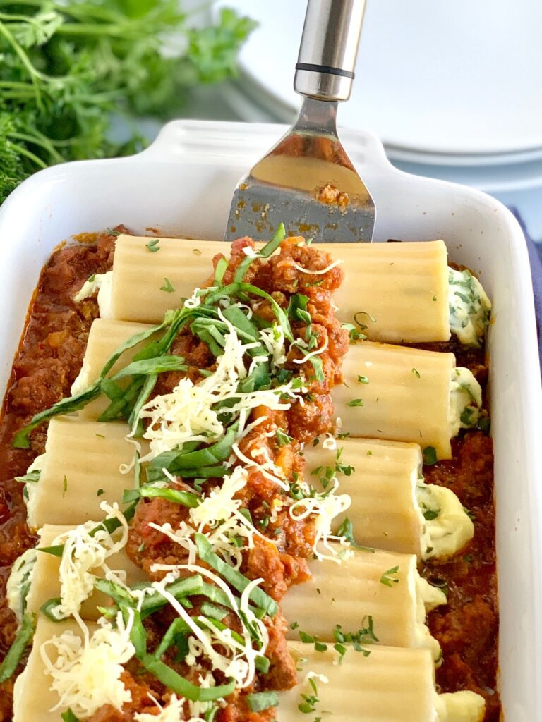 A large white baking dish filled with ground beef and marinara sauce then topped with round pasta shells filled with spinach, and a ricotta mixture. Then that's topped with more ground beef marinara sauce, dairy free cheese shreds, spinach, and fresh parsley with a serving spatula lifting up two of the manicotti out of the pan.