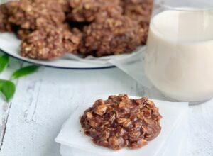 A close up of a No Bake Cookie with chocolate and peanut butter mixture over oats next to a big glass of milk.