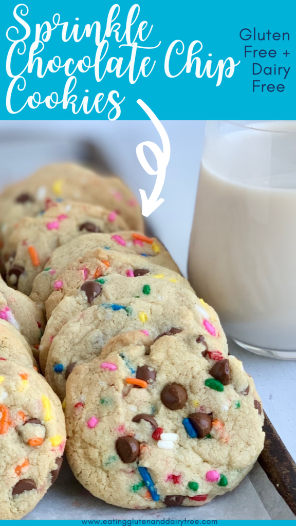 A baking sheet filled with chocolate chip cookies with colorful sprinkles next to a glass of dairy free milk.