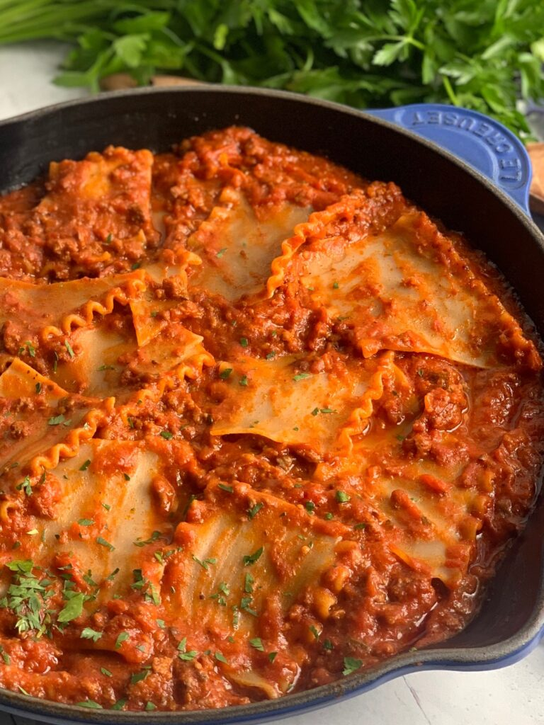 A skillet filled with tender lasagna noodles broken into pieces in a meaty marinara sauce and pieces of fresh parsley over the top.