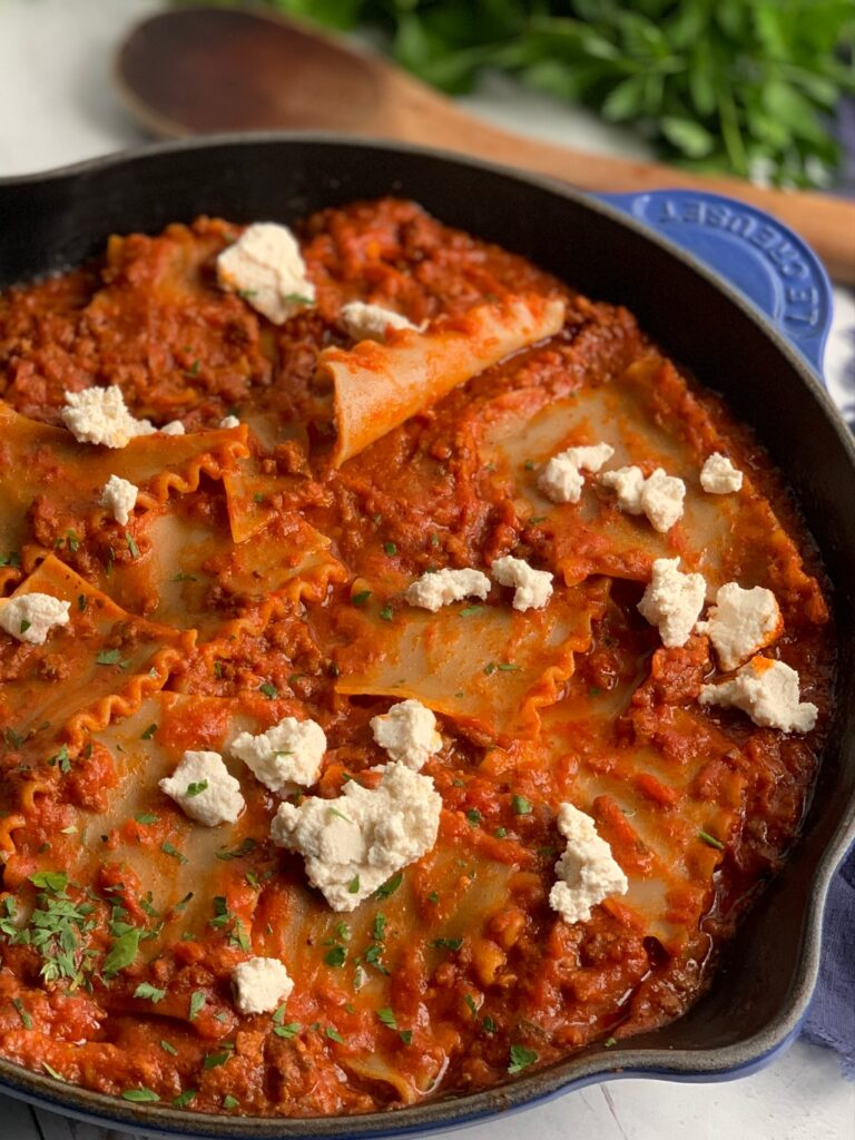 A skillet filled with tender lasagna noodles broken into pieces in a meaty marinara sauce and pieces of ricotta over the top.
