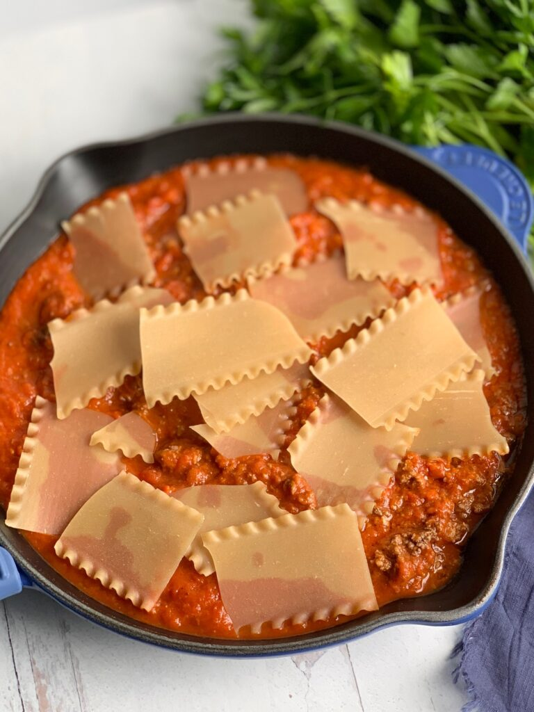 A skillet filled with broken lasagna noodles in a meaty marinara sauce next to a bunch of fresh parsley.