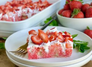 A large slice of vanilla cake with strawberry jello in it with a whipped topping on it and fresh strawberries on that. There is a fork nearby and a bowl of strawberries.