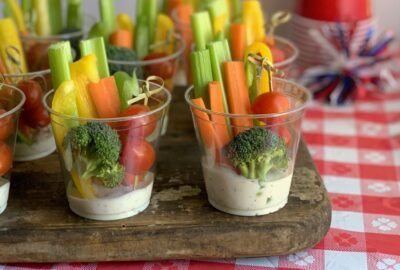 A small party drink cup with white ranch dressing in the bottom. Then sliced celery, carrots, bell peppers in the back of the cup. 3 cherry tomatoes on a fun bamboo skewer in front with a piece of broccoli.