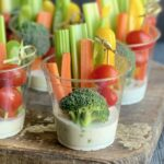 Small party drink cups with white ranch dressing on the bottom of the cup. Celery, carrots, and yellow bell pepper slices are in the back of the cups. Then 3 cherry tomatoes are on a bamboo skewer next to a piece of broccoli.