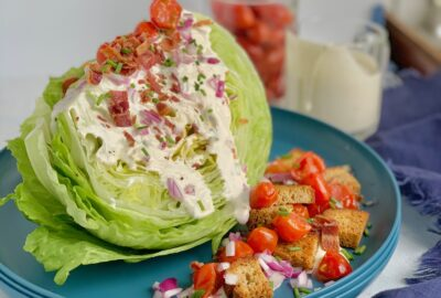 A quartered piece of iceberg lettuce topped with red onion, bacon crumbles, cherry tomatoes sautéed in bacon grease, golden croutons, and ranch dressing drizzled over it on a blue salad plate, In the background is a cup of ranch dressing.
