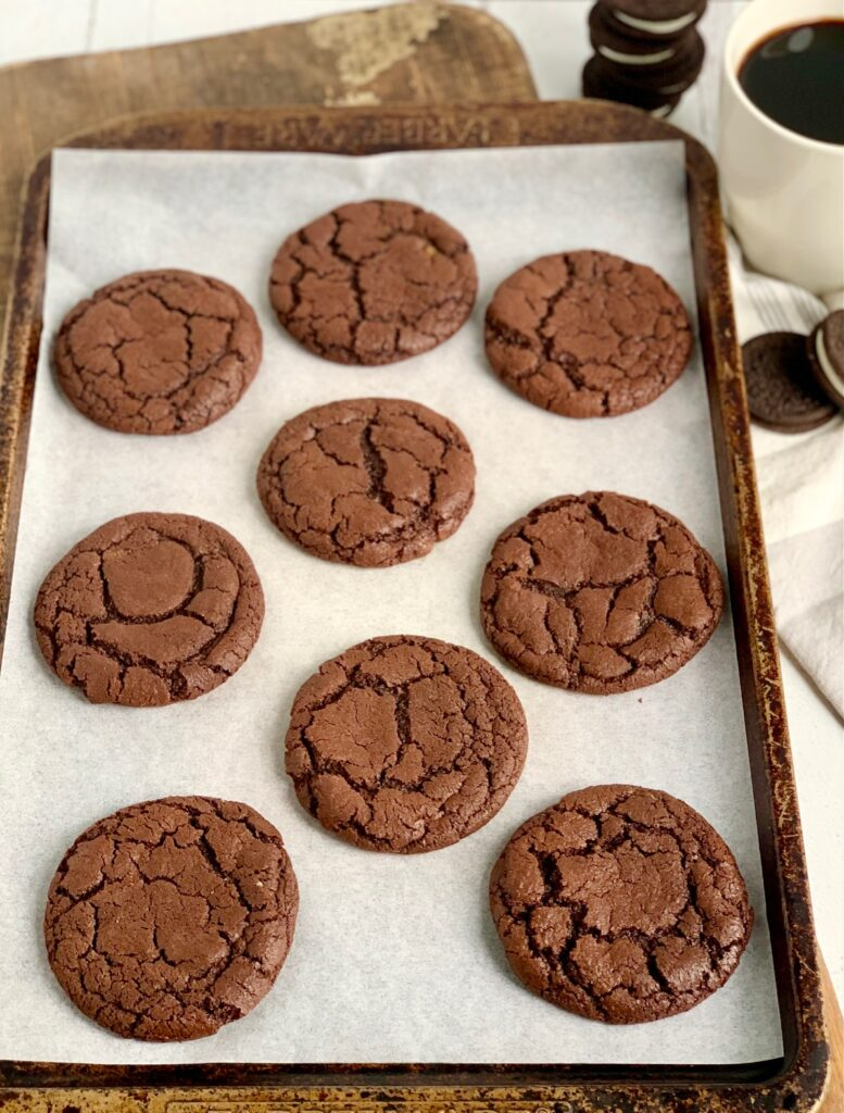 A large cookie sheet with 9 baked brownie cookies on it.