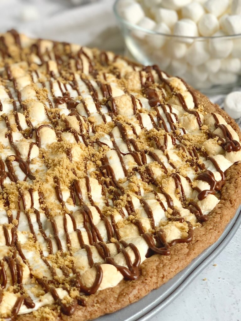 A pizza pan layered with a graham cracker crust, melted chocolate, golden brown mini marshmallows, then drizzled with chocolate and topped with graham cracker crumbs. next to a small bowl overflowing with mini marshmallows.